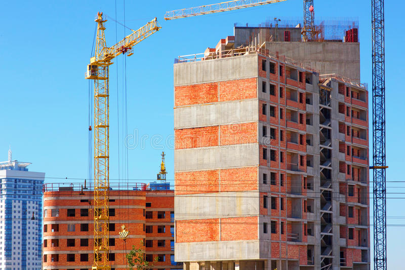 Budujący z podnosić żurawie, basztowi żurawie na budowie budynek obraz royalty free