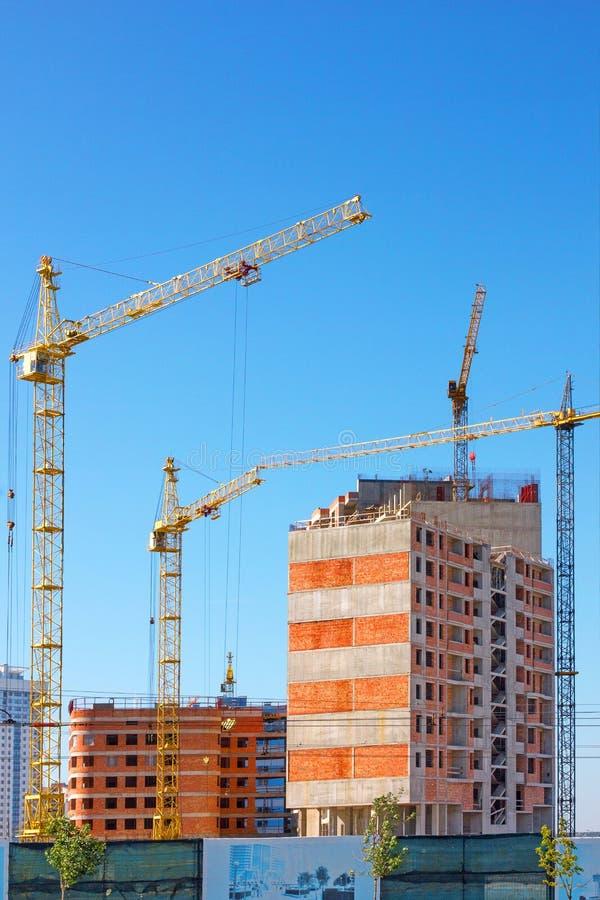 Budujący z podnosić żurawie, basztowi żurawie na budowie budynek zdjęcia stock