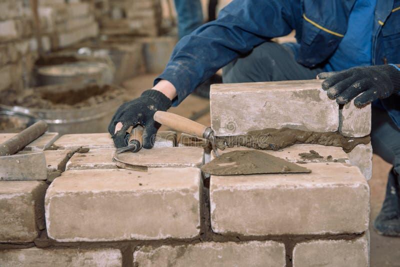 Buduje ścianę cegły Ucznie uczą się kłaść cegły Cementowe niewolne cegły Szpachelka ubijający cement Zawodu budowniczy obraz royalty free