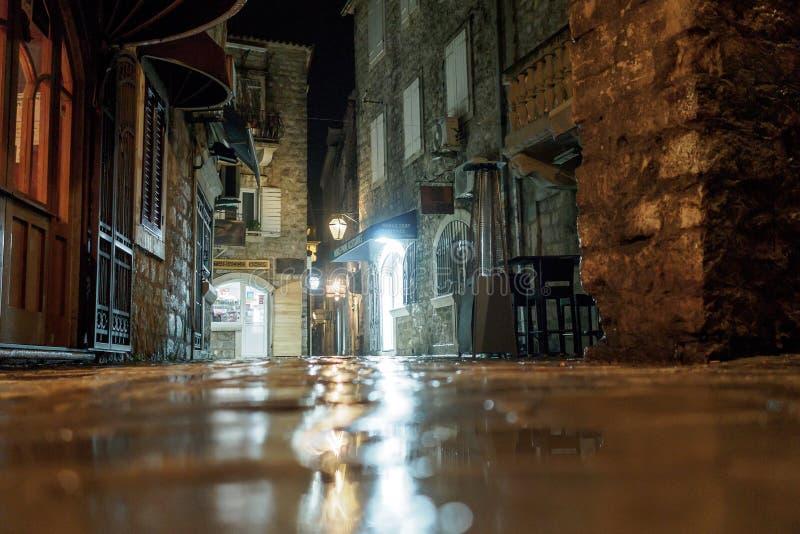 Budva, Черногория - 2-ое февраля 2019 Мощенная булыжником улица старого города загорена вечером светом фонарика стоковые изображения rf