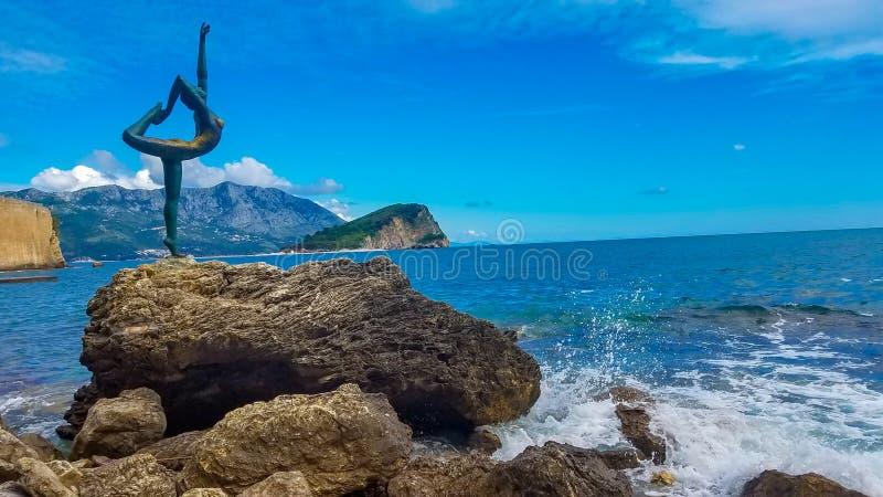 BUDVA, estátua de MONTENEGRO de um dançarino da bailarina de Budva contra a cidade velha de Budva perto da praia de Mogren, Budva imagem de stock