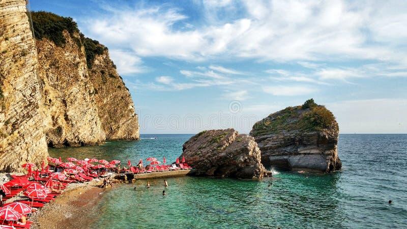 Budva, Montenegro - 11 de agosto de 2018: La gente disfruta del resto en la playa de Mogren Vacaciones de la playa en el mar adri foto de archivo
