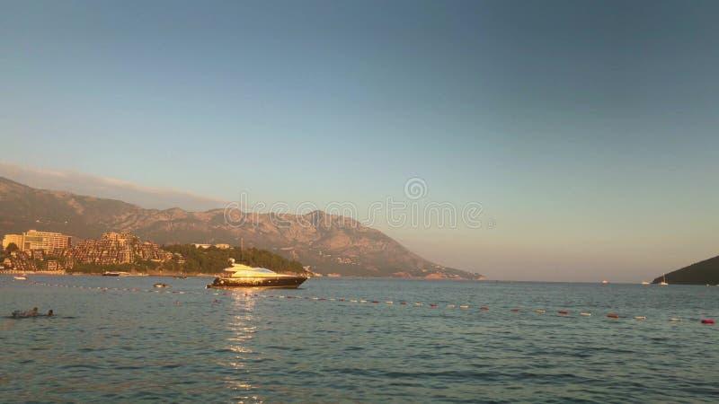 Budva, Montenegro - Juli 30, 2018 Motorjacht tegen Dukley-onroerende goederen Tuinenluxe bij zonsondergang stock afbeelding