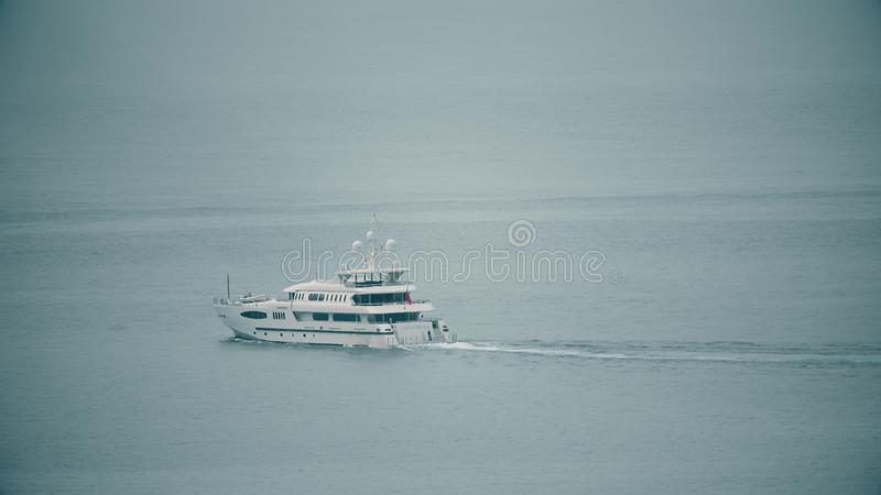 BUDVA MONTENEGRO, LIPIEC, - 26, 2018 Odległy luksusu silnika jacht pływa statkiem przy morzem fotografia stock