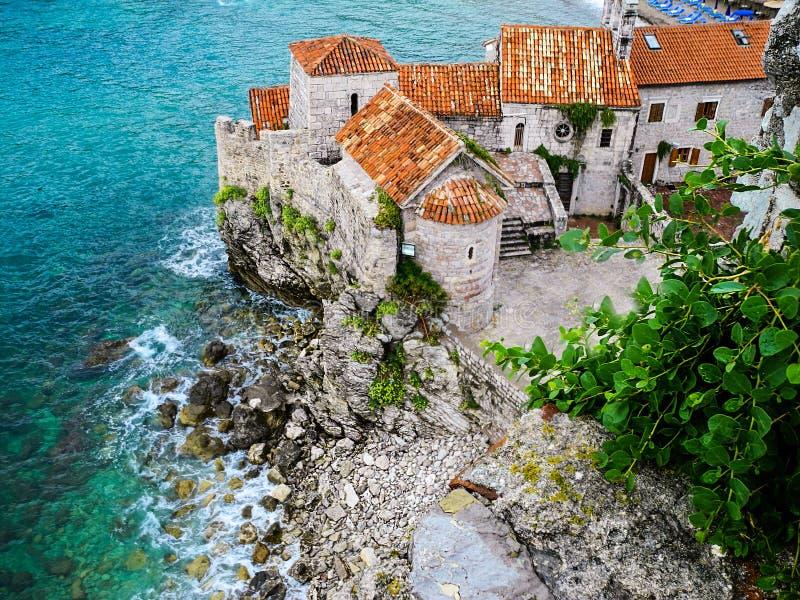 Budva, Montenegro. Turquoise waters of Adriatic sea and orange tile roofs. Budva, Montenegro. Medieval walls and orange tiling roofs and turquoise waters of stock images