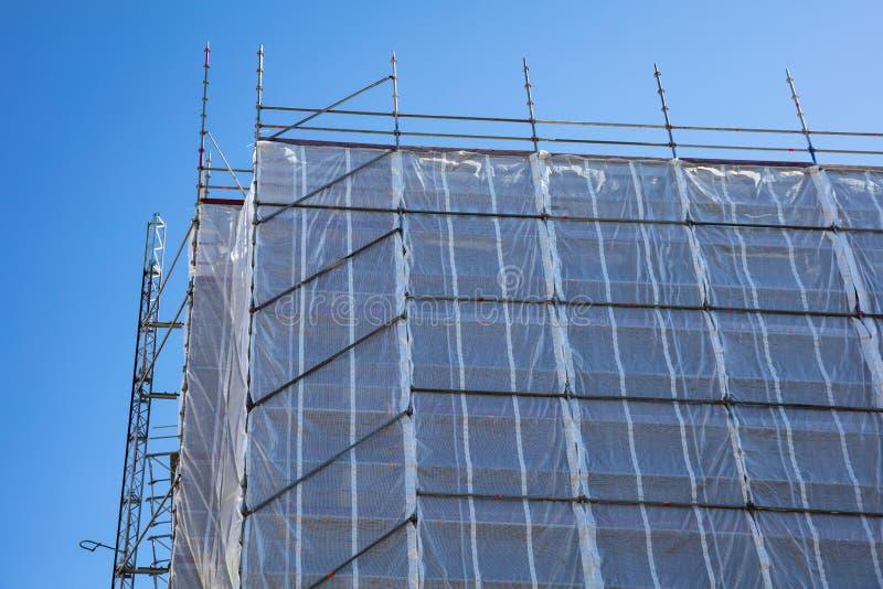 Budynek budowa z rusztowaniem, niebieskiego nieba tło zdjęcia stock