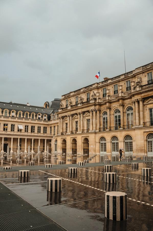 Budynek fasada i wewnętrzny podwórze z ludźmi na deszczowym dniu przy palais royal w Paryż obrazy royalty free
