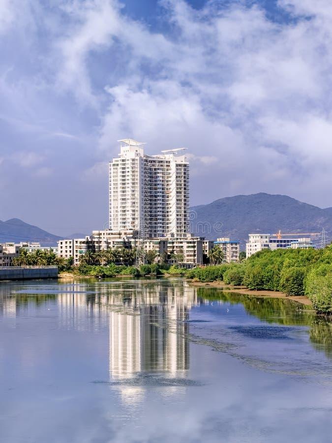 Budynek mieszkaniowy odbijał w rzece na letnim dniu, Sanya, Hainan wyspa, Chiny fotografia royalty free