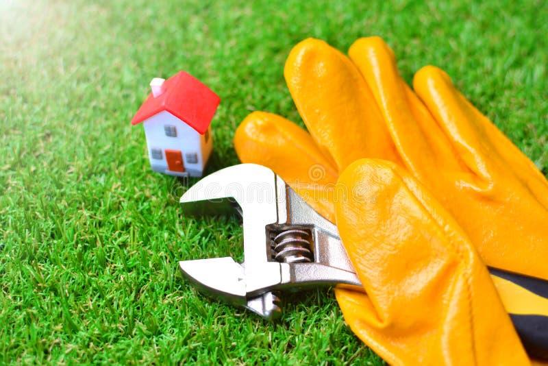 Budynek rękawiczka z nastawczego wyrwania i miniatury domem na zielonej trawie Sanitarnej inżynierii usługi pojęcie obrazy royalty free