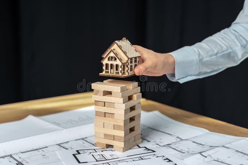 Budynek strategii pojęcie Dama architekt w jej formalwear koszula stojaku wśrodku stacji roboczej, trzyma małego domu przedmiot w obrazy stock