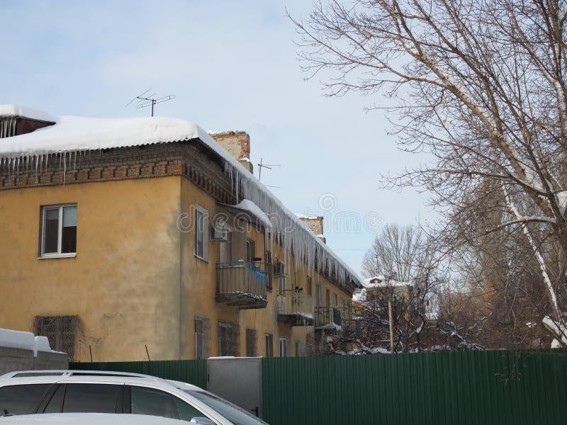 Budynek zakrywający z dużymi soplami Sopla zrozumienie od dachu, pionowo lodowy soplena obwieszenie od dachu obrazy stock