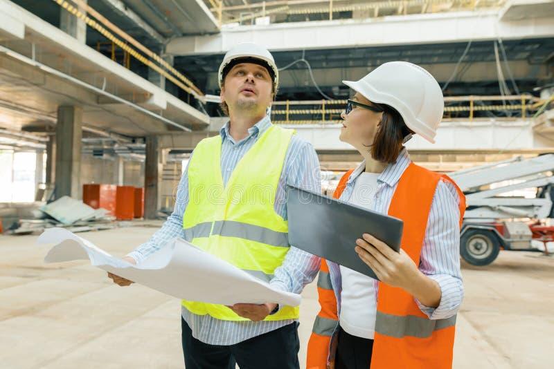 Budynków pracownicy pracuje przy budową, budowniczowie patrzeje w projekcie Budynek, rozwój, praca zespołowa i ludzie pojęć, fotografia stock