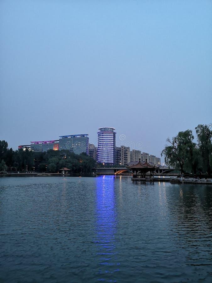 Budynki i zboczeniec ocieniają z światłami w rzece fotografia royalty free