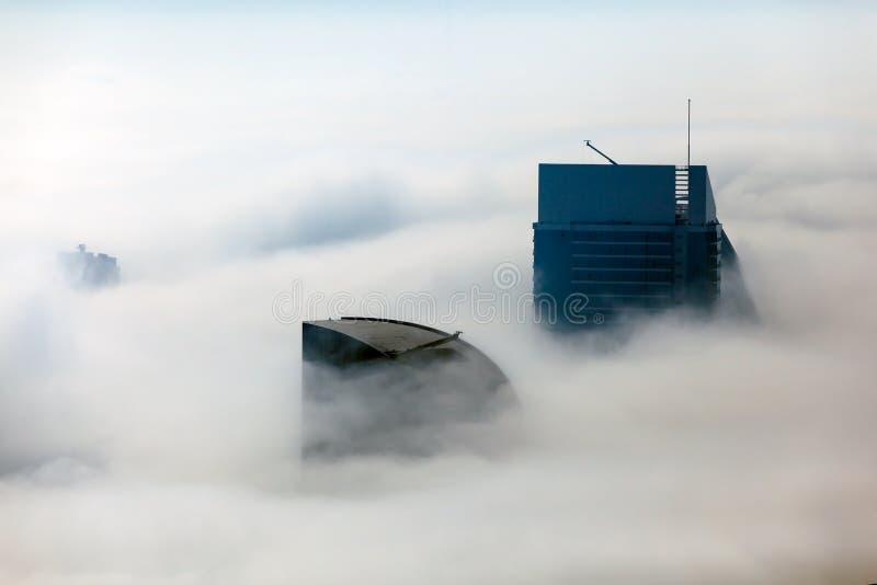Budynki zakrywają w gęstej warstwie mgła fotografia royalty free