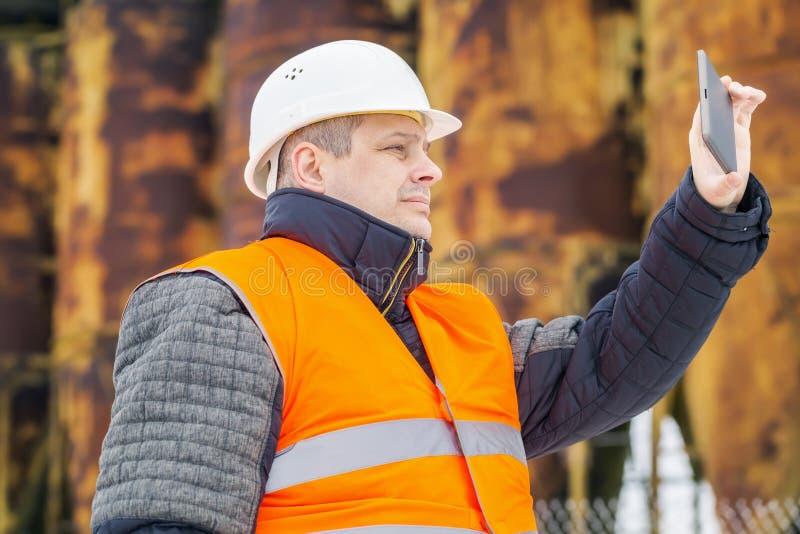 Budynku inspektor filmujący z pastylka pecetem blisko fabryki zdjęcie royalty free