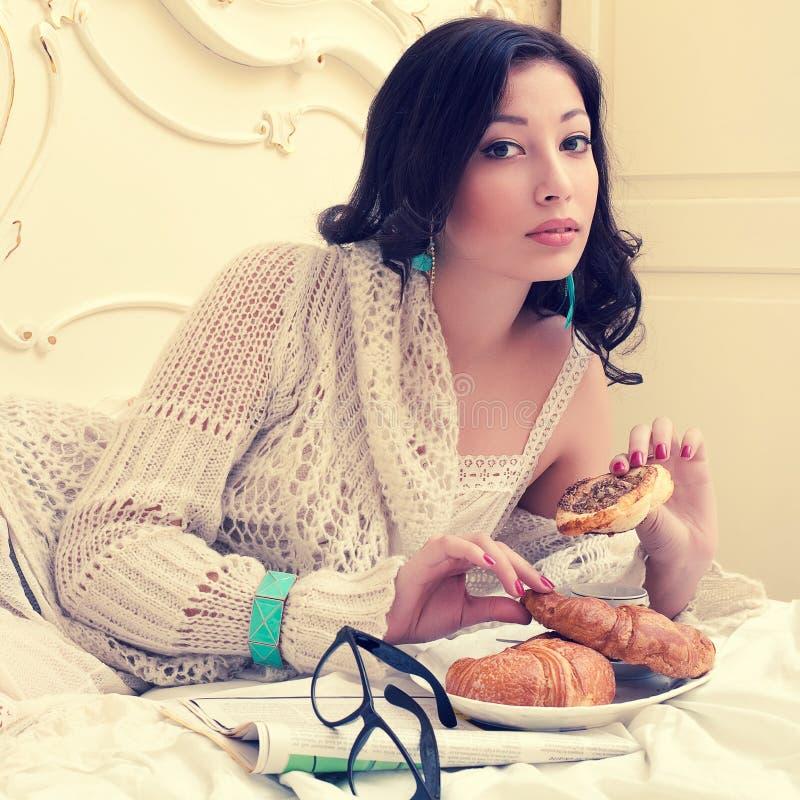 Budzący emocje portret młoda piękna kobieta je jej croissant fotografia royalty free