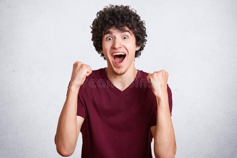 Budzący emocje rozradowany męski nastolatek zaciska pięści, kędzierzawego ciemnego włosy, jest ubranym przypadkową t koszula, poz obraz royalty free