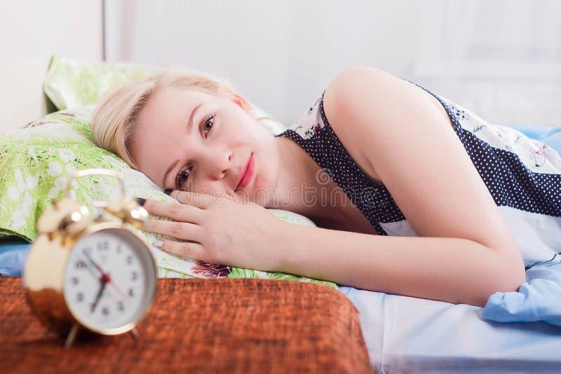 Budzący się uśmiechniętego młodego blondynki kobiety lying on the beach w łóżku w jaskrawej sypialni w domu, ranku pojęcie Zegar  fotografia stock