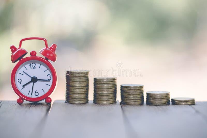 Budzik i krok monet sterty na stole, czas dla oszczędzanie pieniądze pojęcia, bankowość i biznes, rocznika brzmienie zdjęcie royalty free