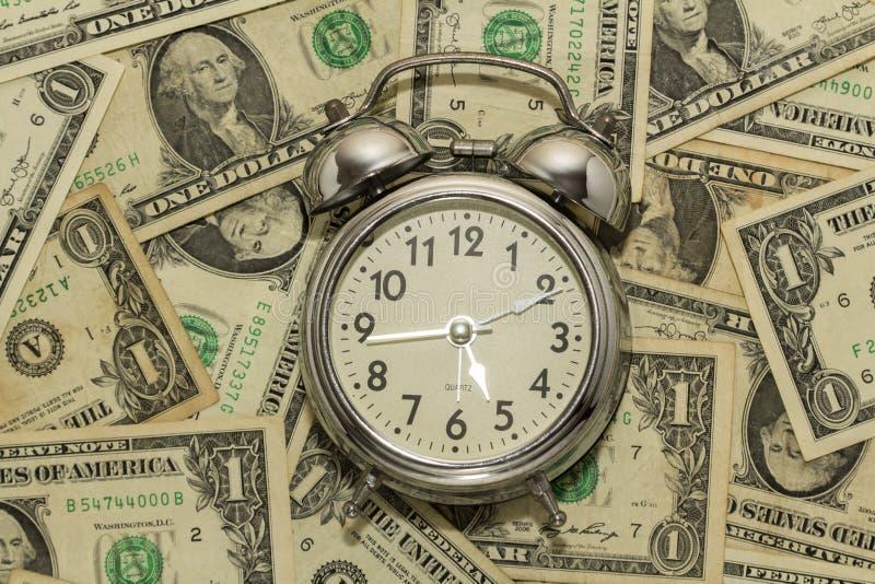 Budzik na dywanie dolarowi rachunki, czas jest pieniądze obraz stock