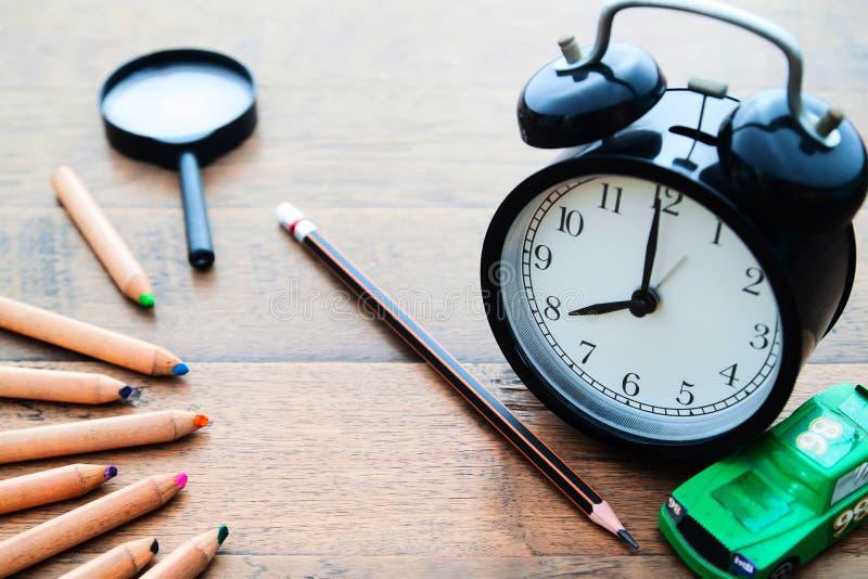 Budzik, ołówek i kolorów ołówki na drewnianym biurku sc, Z powrotem zdjęcie stock