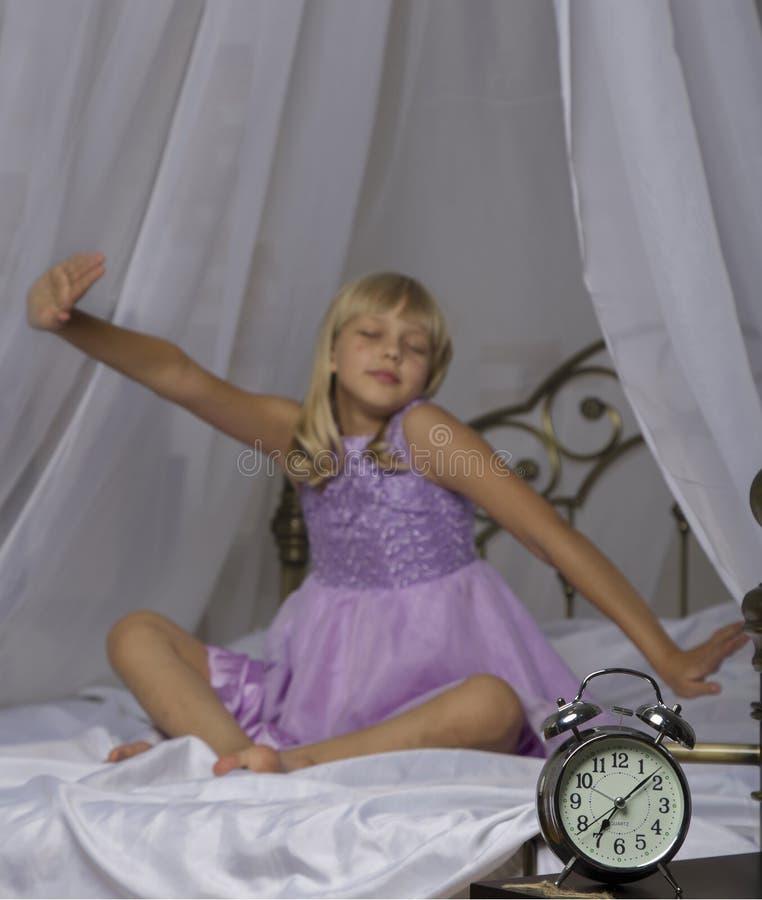 Budzik pozycja na wezgłowie stole Budził się uśpiona młoda dziewczyna rozciąga w łóżku w tle zdjęcie royalty free