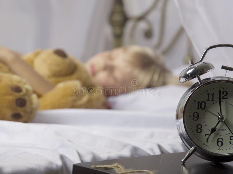 Budzik pozycja na wezgłowie stole Budził się uśpiony młodej dziewczyny powstrzymywania budzik na łóżku w ranku fotografia stock