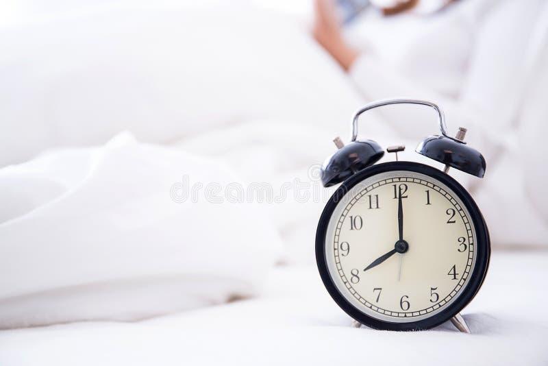 budzik pozycja na wezgłowie stole iść dzwonić wczesnego poranek zdjęcie stock