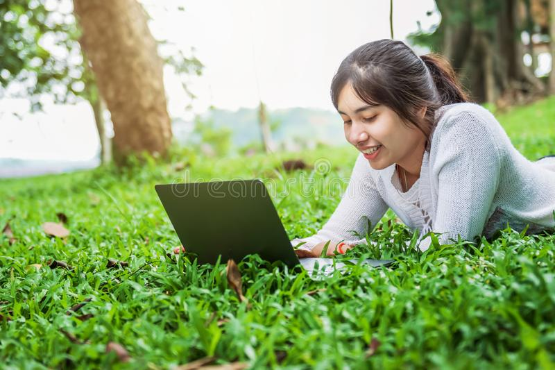 bueatiful woman with laptop on green grass in park stock photo