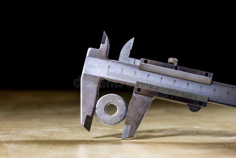 Buen calibrador viejo a disposición mientras que mide el abdomen Etiqueta de madera foto de archivo libre de regalías