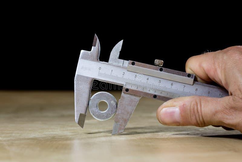 Buen calibrador viejo a disposición mientras que mide el abdomen Etiqueta de madera fotos de archivo libres de regalías
