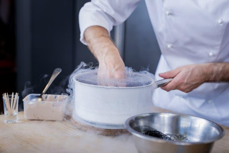 Buen cocinero que muestra sus habilidades en gastronomía molecular imagenes de archivo