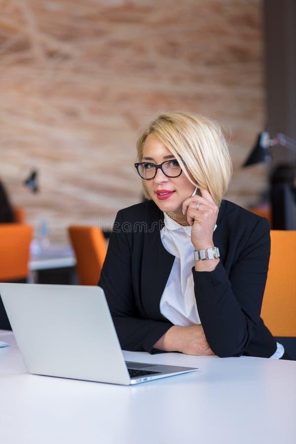 Buena charla del negocio Mujer hermosa joven alegre en vidrios que habla en el teléfono móvil y que usa el ordenador portátil fotos de archivo