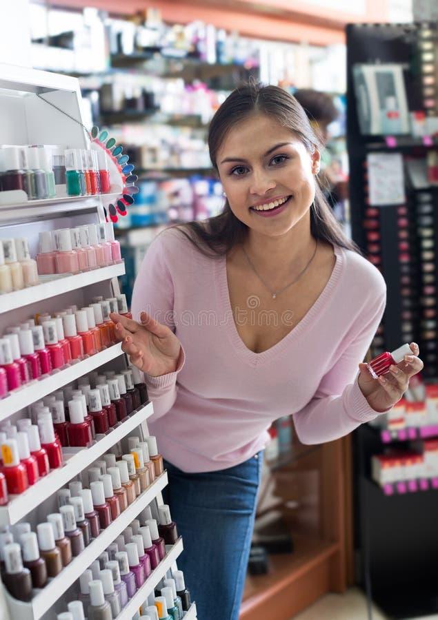 Buena chica joven que elige esmalte de uñas fotografía de archivo libre de regalías