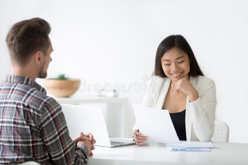 Buena impresión en el concepto de la entrevista, hora asiática sonriente que lee r imagen de archivo