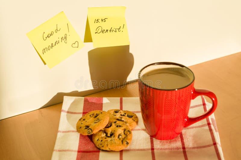 BUENA MAÑANA de la etiqueta engomada, DENTISTA en la tabla en casa Fondo - mantel con la taza de café y de galletas fotos de archivo