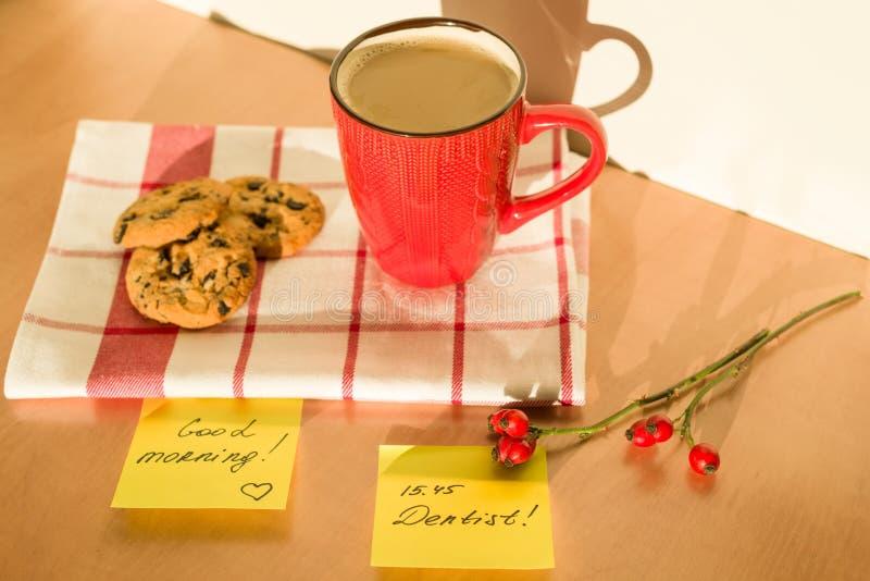 BUENA MAÑANA de la etiqueta engomada, DENTISTA en la tabla en casa Fondo - mantel con una taza de café y de galletas imagen de archivo libre de regalías
