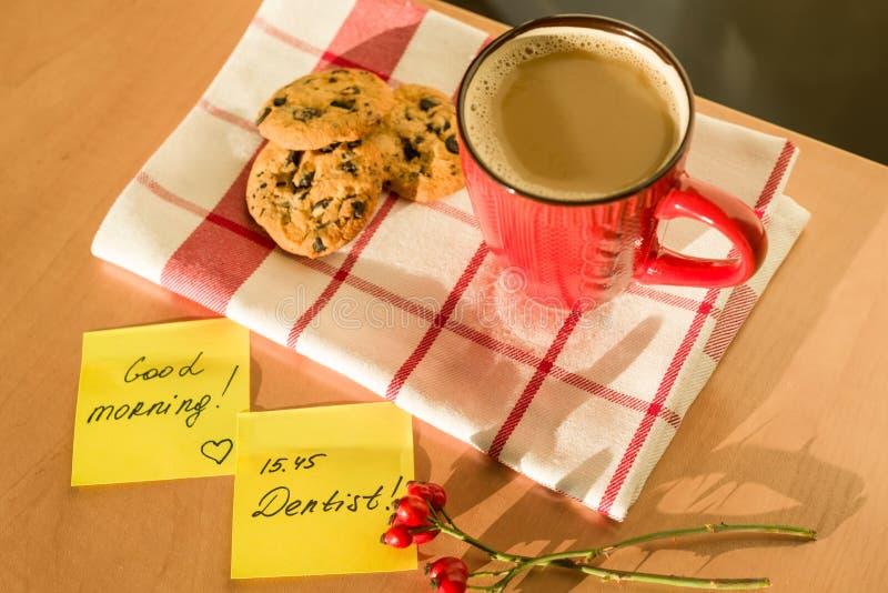 BUENA MAÑANA de la etiqueta engomada, DENTISTA en la tabla en casa Fondo - mantel con una taza de café y de galletas fotografía de archivo libre de regalías