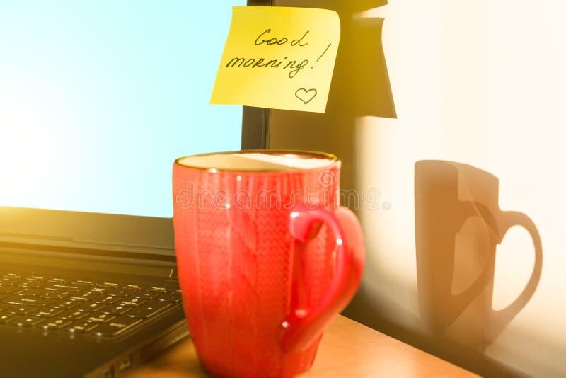 BUENA MAÑANA de la etiqueta engomada en fondo del Otoño-invierno del desayuno del ordenador portátil imagenes de archivo