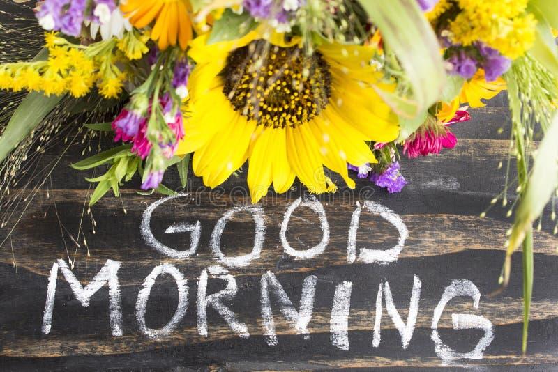 Buena mañana de las palabras con las flores del verano en un Backgr de madera rústico imagen de archivo