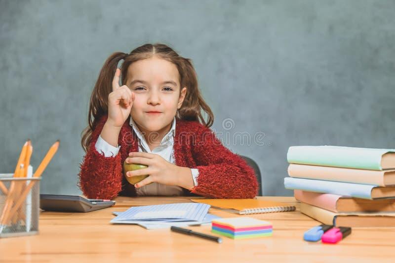 Buena muchacha misma de la colegiala que se sienta en la tabla Durante esto, él sostiene una manzana verde en su mano, con la otr fotos de archivo