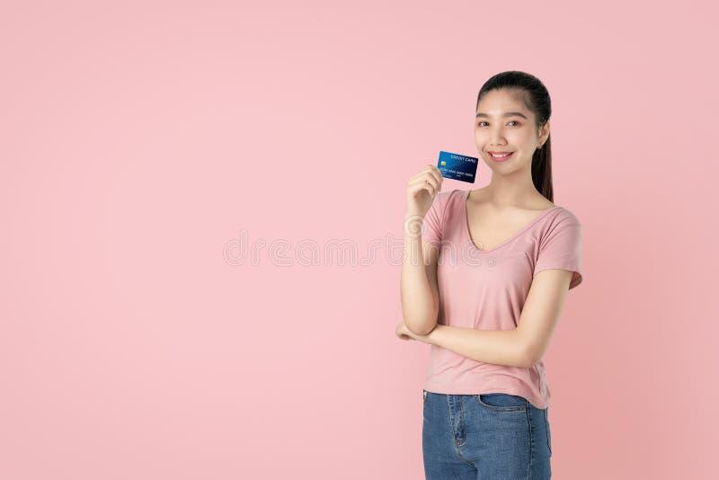 Buena piel de la mujer asiática hermosa que lleva a cabo el pago con tarjeta de crédito en fondo rosado con el espacio de la copi fotografía de archivo