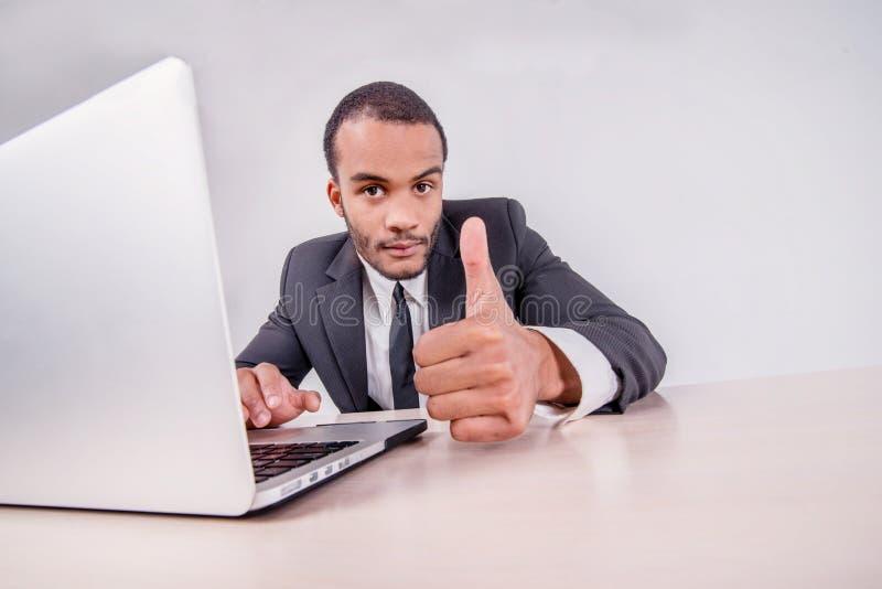 Buena suerte a usted Hombre de negocios africano sonriente que se sienta en un escritorio foto de archivo
