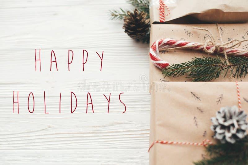 Buenas fiestas texto en presentes elegantes de la Navidad con ribbo rojo imagen de archivo