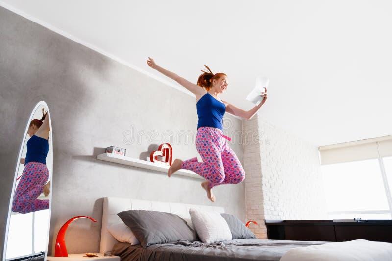 Buenas noticias para la muchacha feliz de la mujer joven que salta en cama fotografía de archivo libre de regalías