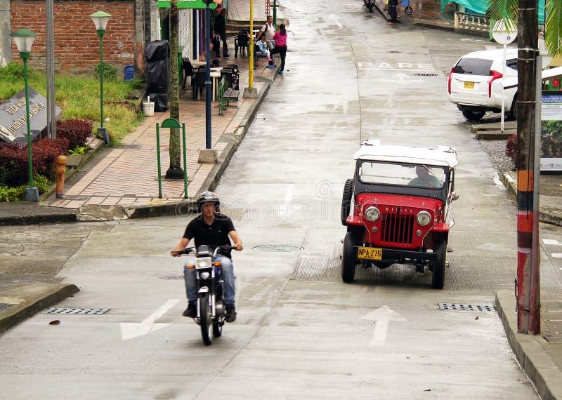 BUENAVISTA, COLOMBIA - AUGUSTUS 14, 2018: Straatscène in Buenavista - Quindio Een bromfiets en een Willys-Jeep op de straat royalty-vrije stock fotografie