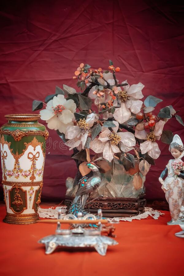 BUENOS AIRES, ARGENTINA - Oct 10, 2019: Vertical shot of artificial flowers with a small female statue and a vase on a red. BUENOS AIRES, ARGENTINA - Oct 10 stock image