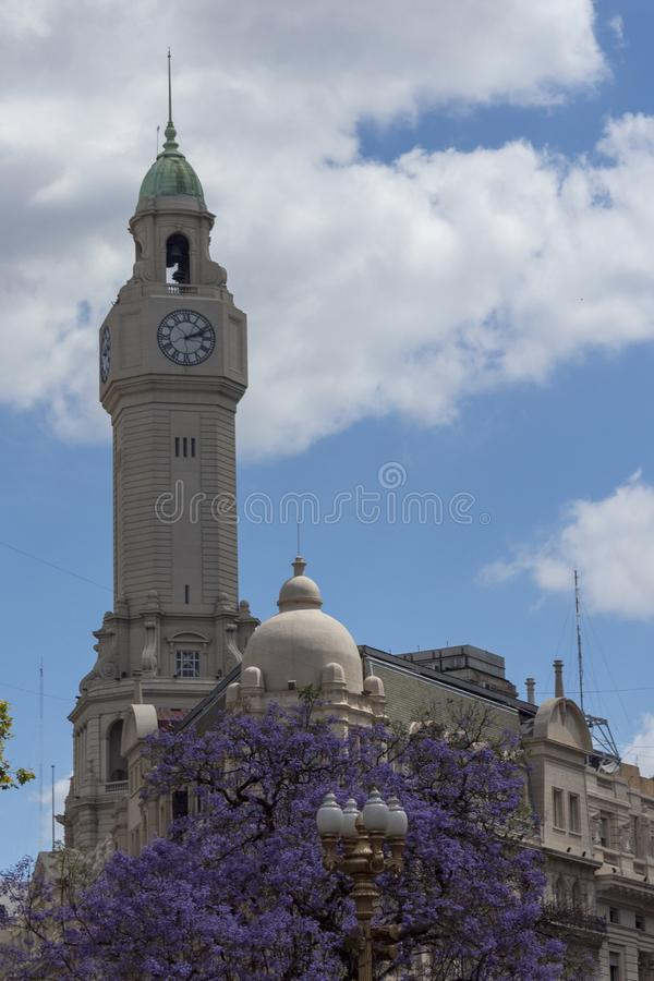 Buenos Aires business district has European feel. Clock Tower behind purple jacarandas in Bloom in Buenos Aires Argentina. Blue summer skies and spongy clouds do stock image