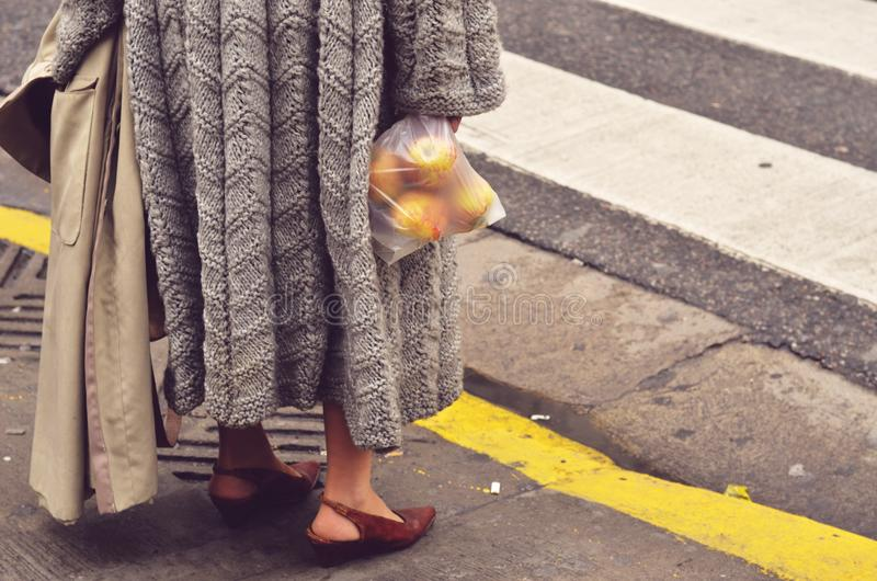 Buenos Aires street style. Everydayness. An old woman walking trough the street getting back from the vegetable market. Vintage scene on lilac and yellow colors royalty free stock image