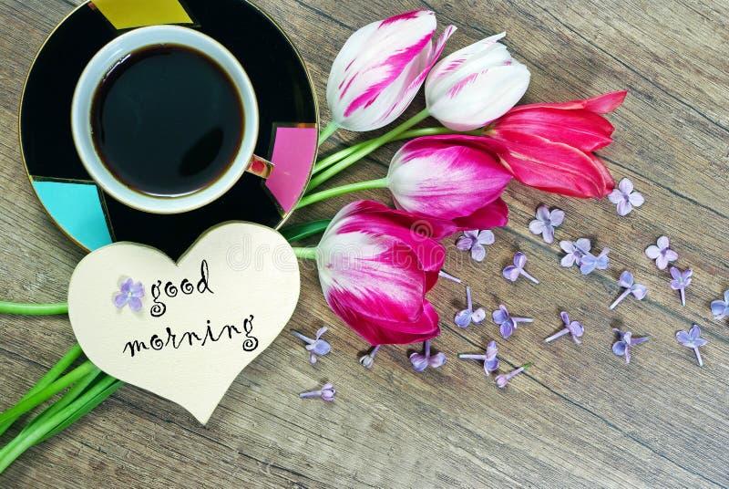 Buenos días café y tulipanes de la mañana en una tabla de madera imagenes de archivo